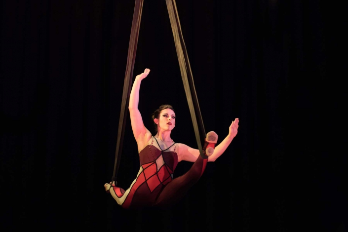 photo of a woman performing a split on aerial straps
