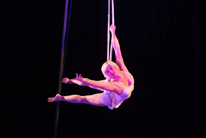 photo of a woman performing on a dance trapeze in a white costume on a black stage