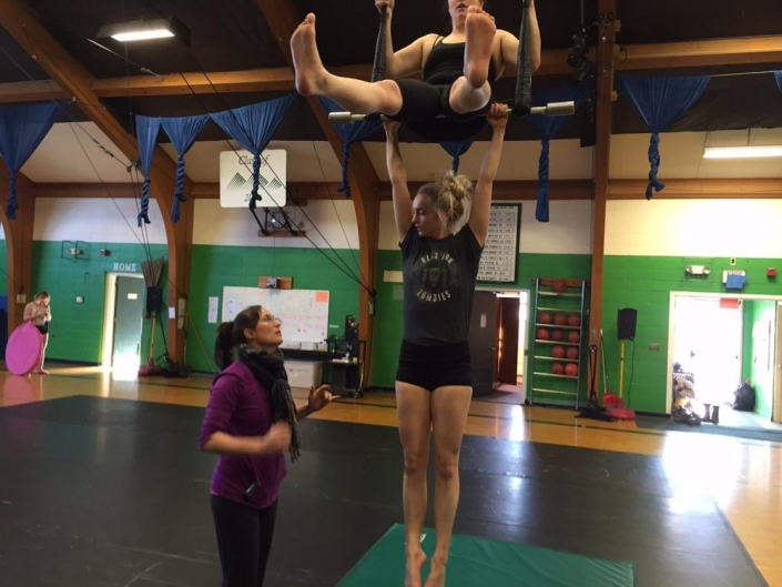 photo of two ProTrack Program students training with a coach on duo trapeze